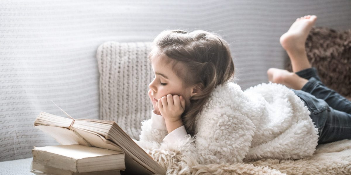 little girl reading a book on a comfortable sofa in a cozy living room at home, beautiful emotions, the concept of relaxation